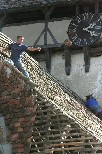 Egy munkás jó állapotú cserepet dob le az egyik templom tetejéről. Műemlék épületek cserepeinek megrongálását törvény tiltja. Fotó: Luke-Dale Harris