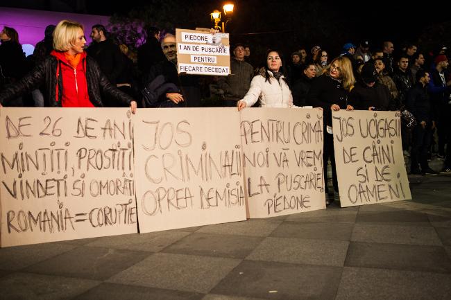 """Feliratok: """"26 éve hazudtok, elárultok és gyilkoltok"""", """"Le a gyilkosokkal, Oprea, mondj le!"""", """"Gyilkosságért börtönbe veletek"""", """"Le a kutyák és emberek gyilkosaival"""". Fotó: Ana Poenariu"""