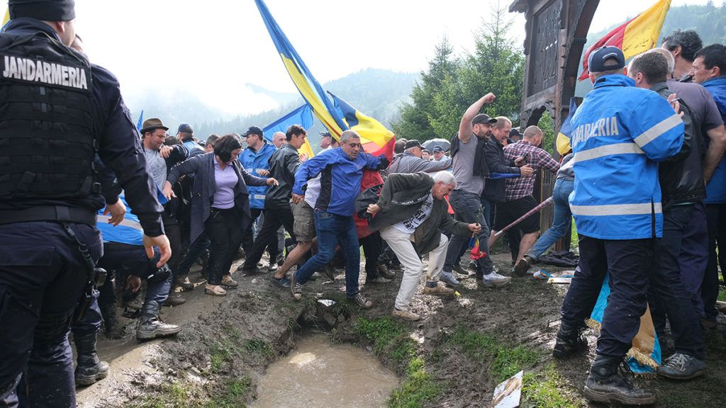 Csendőrökkel dulakodnak román résztvevők, akik erőszakkal benyomult az úzvölgyi katonatemetőbe, ahol ortodox szertartás keretében felszentelték törvénysértően létesített román emlékművet és parcellát 2019. június 6-án. Fotó: Veres Nándor / MTI