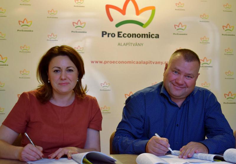 Balázs László, reprezentantul Batlas Holding și Plazmontech (în dreapta) și Kozma Mónika, directoarea executivă a Fundației Pro Economica, semnează contractul de finanțare. Sursa: pagina de Facebook Pro Economica